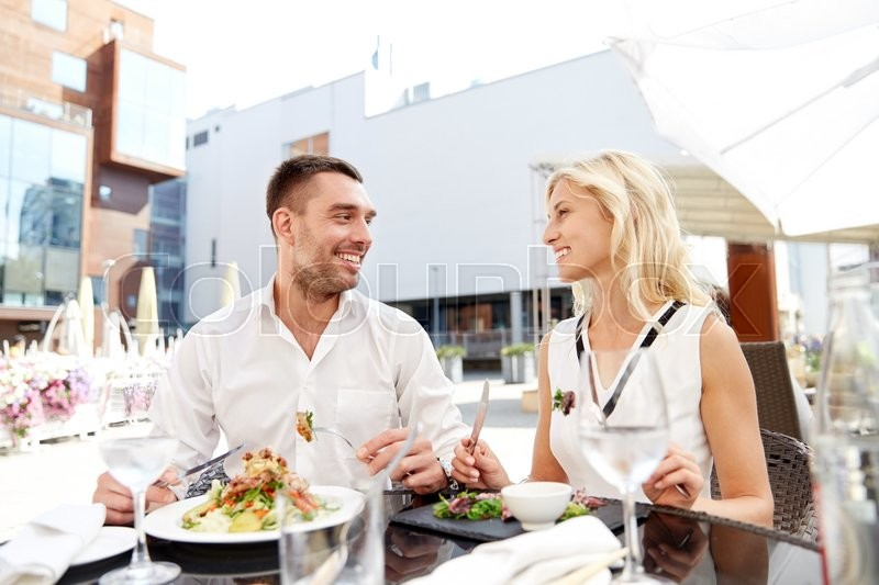 Stock image of 'love, date, people, holidays and relations concept - happy couple eating salad for dinner at cafe or restaurant terrace'