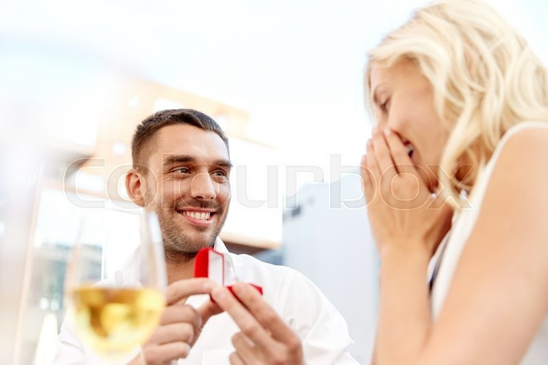 Stock image of 'love, anniversary, surprise, people and holidays concept - happy man with engagement ring making proposal to woman at restaurant'