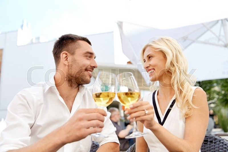 Stock image of 'love, dating, people and holidays concept - happy couple drinking wine at open-air restaurant and clinking glasses'