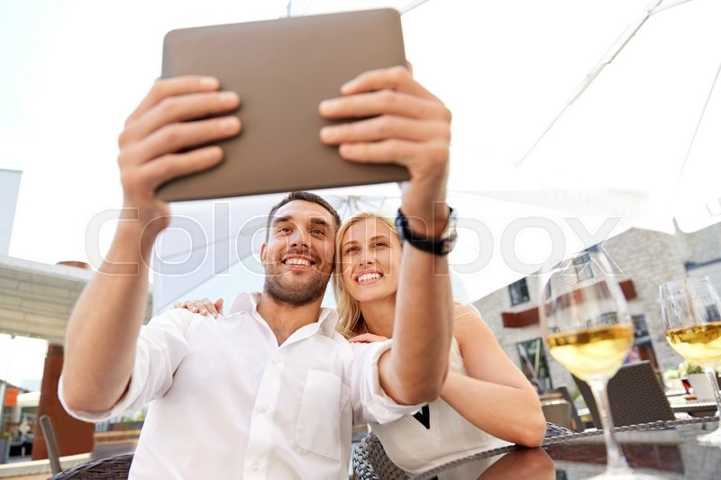 Stock image of 'love, date, technology, people and relations concept - smiling happy couple taking selfie with tablet pc computer at restaurant terrace'