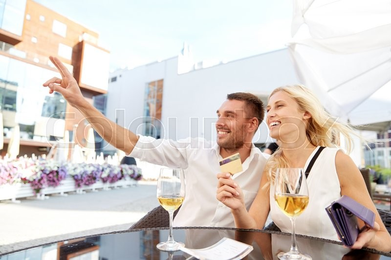 Stock image of 'date, people, payment and finances concept - happy couple with wallet, credit card and wine glasses calling waiter for bill payment at restaurant'