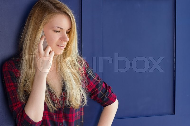 Stock image of 'Pretty Woman Calling Someone Through Mobile Phone While Smiling at the Camera Against Blue Wall Background'