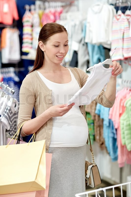 Stock image of 'pregnancy, people, sale and expectation concept - happy pregnant woman with shopping bag buying baby bodysuit at children clothing store'