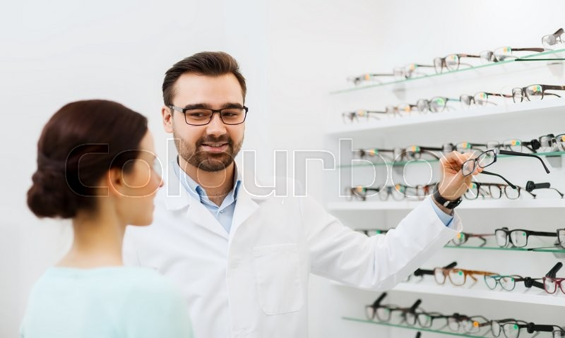 Stock image of 'health care, people, eyesight and vision concept - optician showing glasses to woman at optics store'