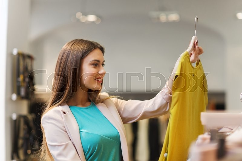 Stock image of 'sale, shopping, fashion, style and people concept - happy young woman choosing clothes in mall or clothing store'