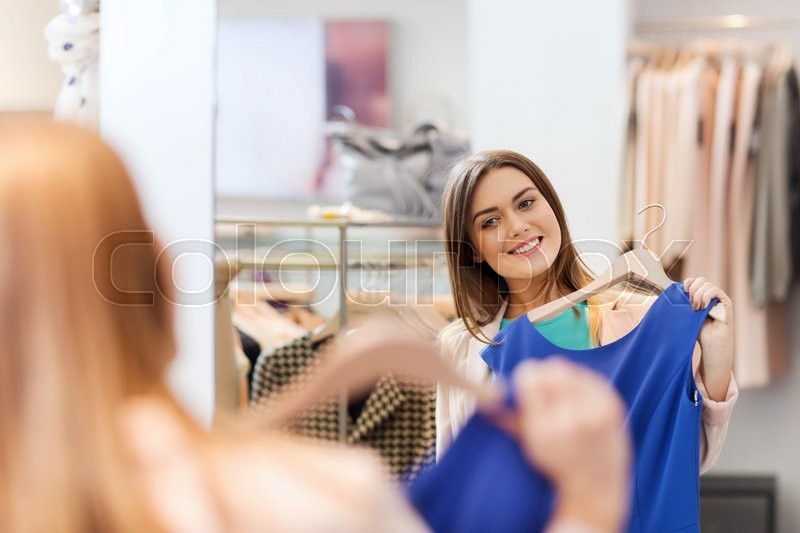 Stock image of 'shopping, fashion, style and people concept - happy woman choosing clothes and looking to mirror in mall or clothing store'