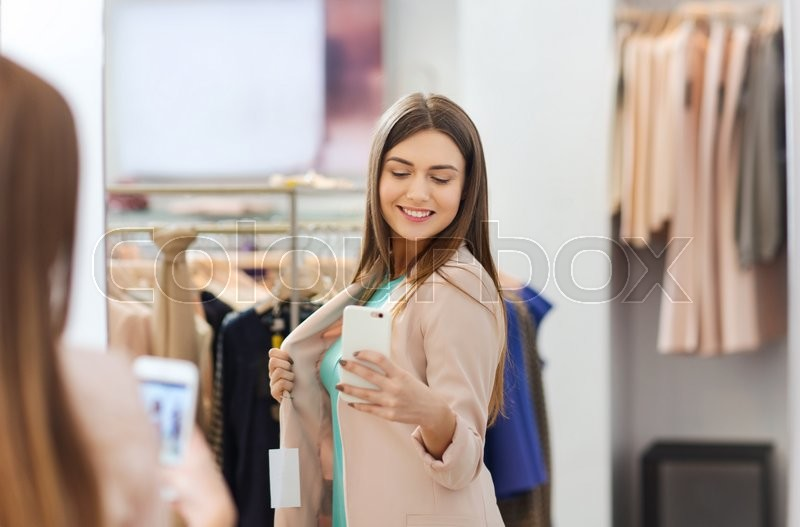 Stock image of 'shopping, fashion, style, technology and people concept - happy woman with smartphone taking mirror selfie at clothing store'