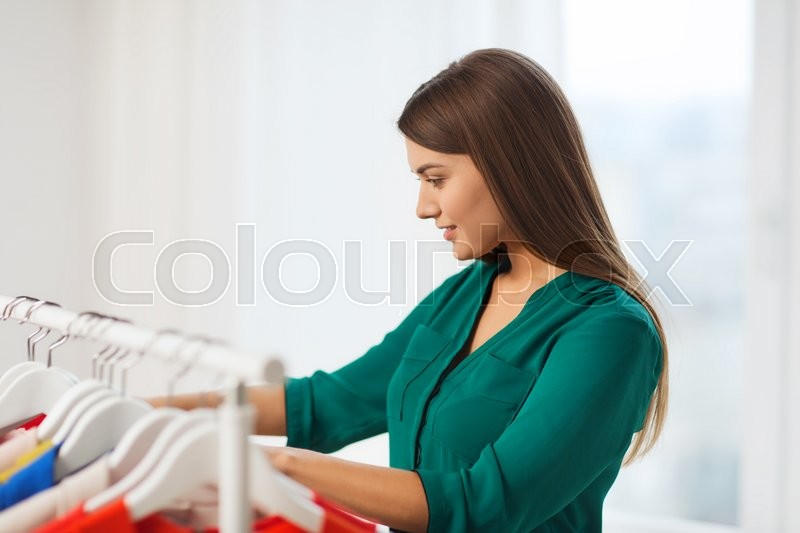 Stock image of 'clothing, fashion, style and people concept - happy woman choosing clothes at home wardrobe'