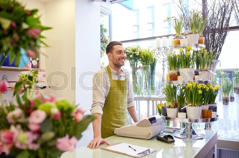 Stock image of 'people, sale, retail, business and floristry concept - happy smiling florist man with clipboard and cashbox standing at flower shop counter'
