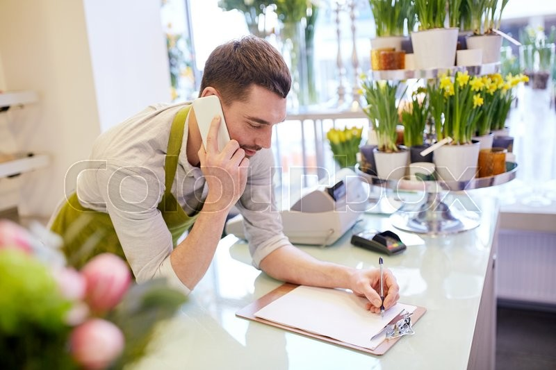 Stock image of 'people, sale, retail, business and floristry concept - happy smiling florist man calling on smartphone and making notes to clipboard at flower shop counter'