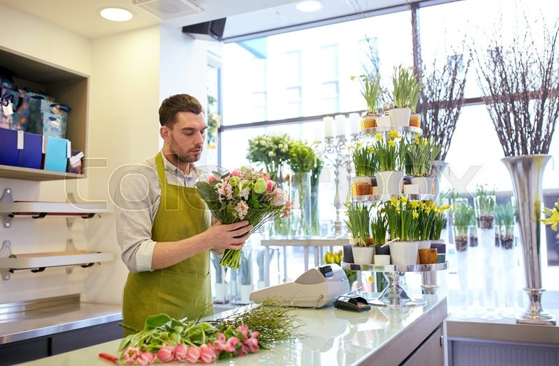 Stock image of 'people, business, sale and floristry concept - florist man making bunch at flower shop'