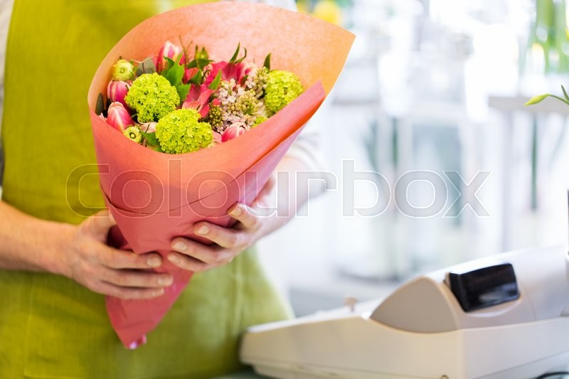 Stock image of 'people, shopping, sale, floristry and consumerism concept - close up of florist man holding bunch wrapped in paper at flower shop cashbox'