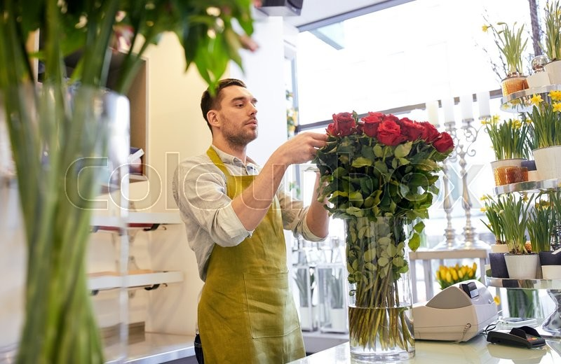 Stock image of 'people, business, sale and floristry concept - happy smiling florist man with red roses at flower shop'