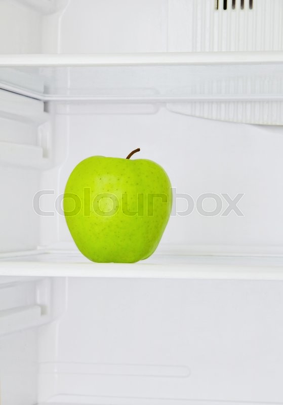 Stock image of 'Lifestyle concept.Big green apple in domestic refrigerator taken closeup.Toned image.'