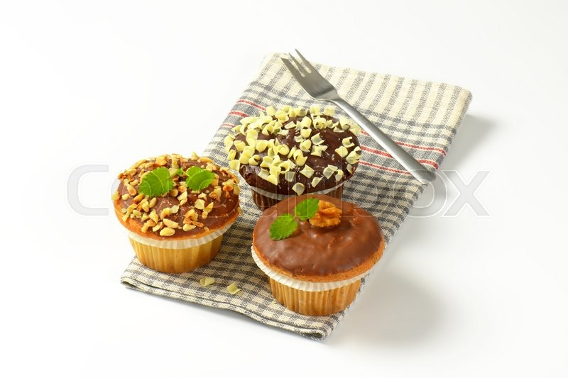 Stock image of 'Assorted muffins - one chocolate muffin, two muffins with nuts'