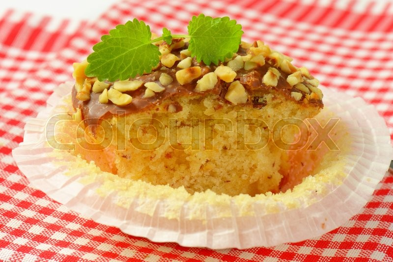 Stock image of 'Muffin topped with chocolate and chopped nuts'