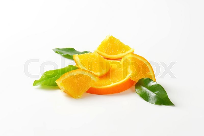 Stock image of 'Pieces of fresh orange with leaves'