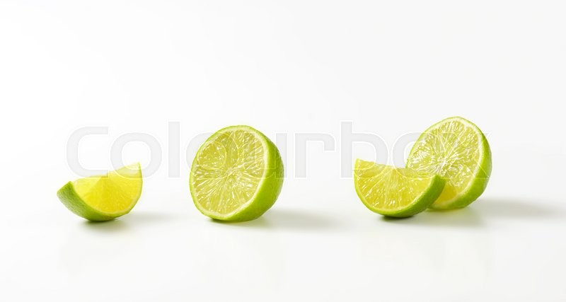 Stock image of 'Fresh lime fruit halves and wedges'