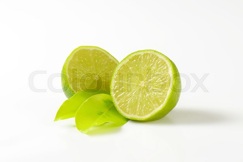 Stock image of 'halved lime and leaves on white background'