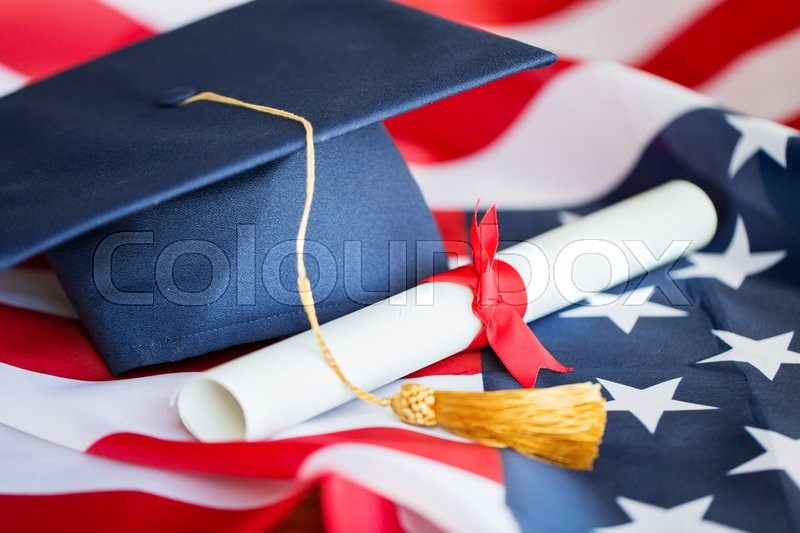 Stock image of 'education, graduation, patriotism and nationalism concept - close up of bachelor hat and diploma on american flag'