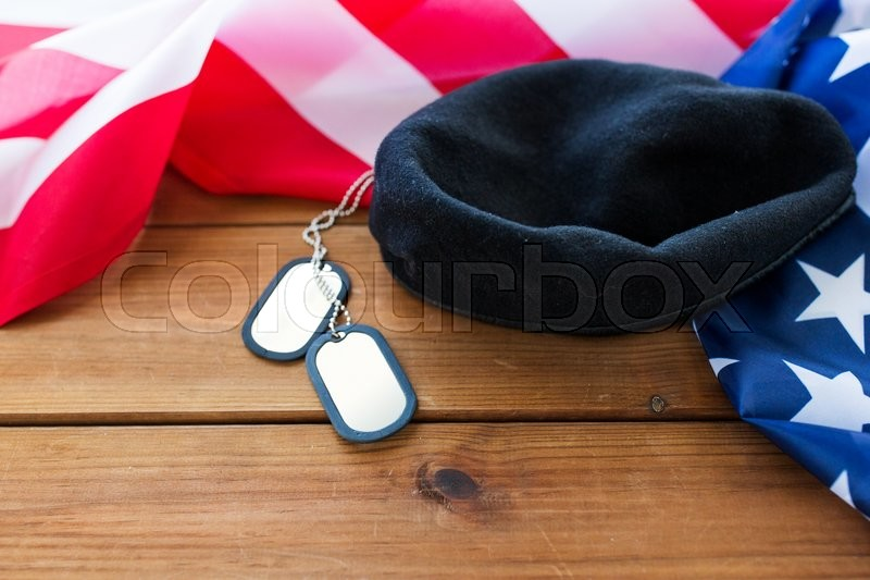 Stock image of 'military forces, service, patriotism and nationalism concept - close up of american flag, soldiers badges and paratrooper hat on wood'