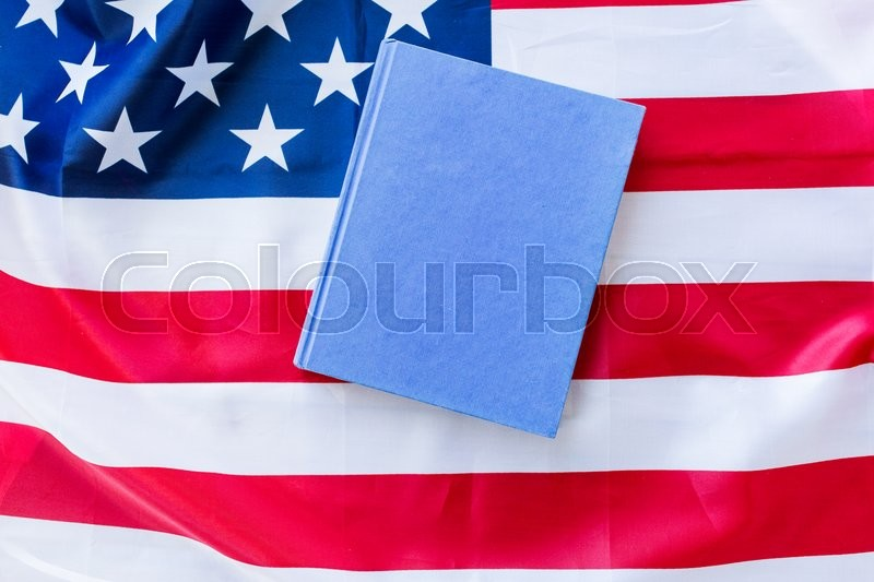 Stock image of 'american independence day, patriotism and nationalism concept - close up of american flag and book'