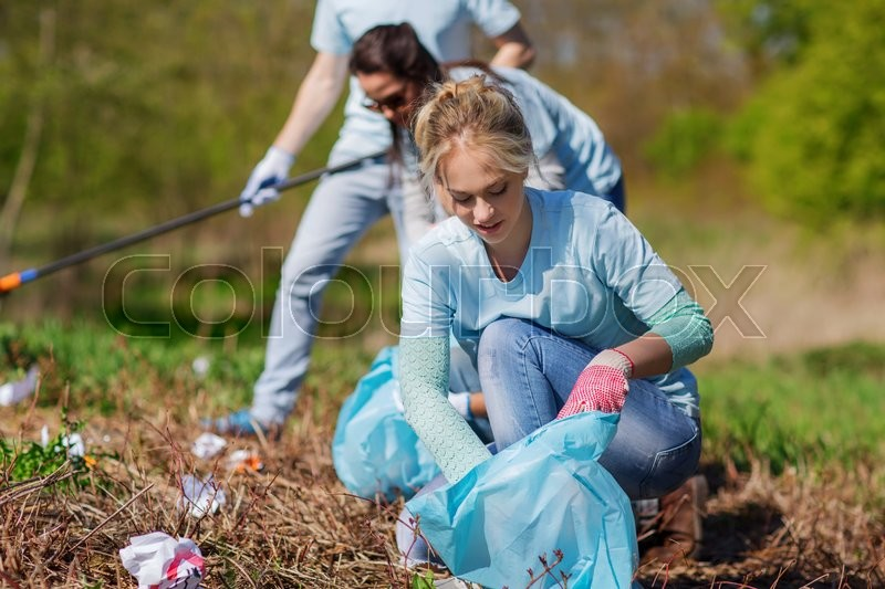 Stock image of 'volunteering, charity, cleaning, people and ecology concept - group of happy volunteers with garbage bags cleaning area in park'