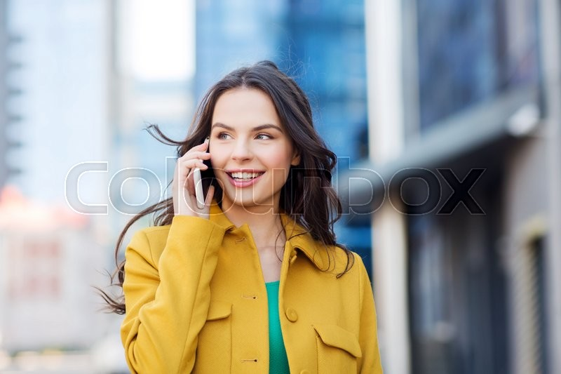 Stock image of 'technology, communication and people concept - smiling young woman or girl calling on smartphone on city street'