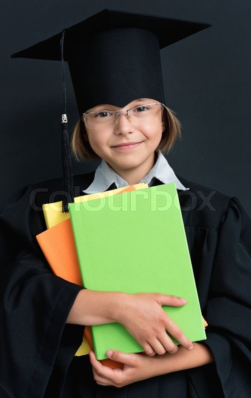 Stock image of 'Smart schoolgirl in glasses and academic hat stands with books at the blackboard'