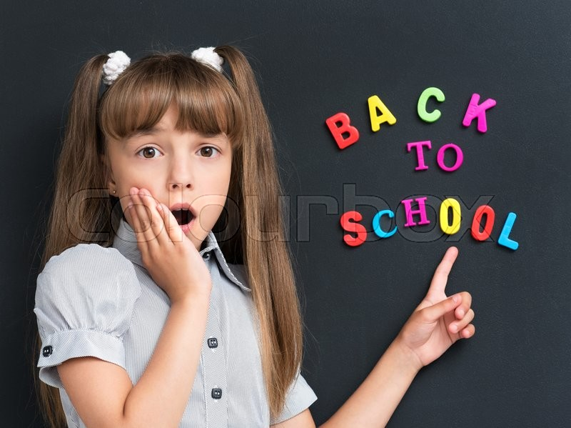 Stock image of 'Back to school concept. Shocked schoolgirl at the chalkboard.'