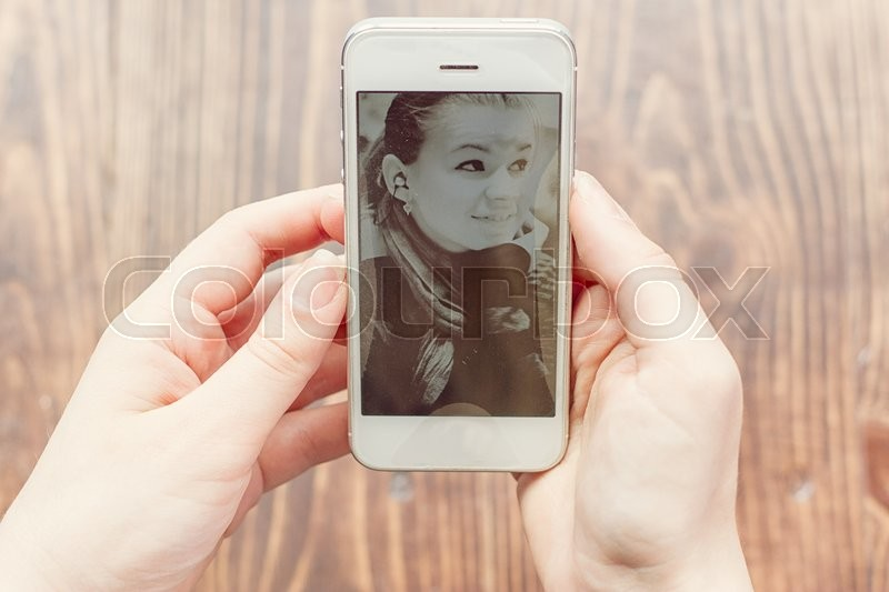 Stock image of 'Girl looks at the phone with her photos'