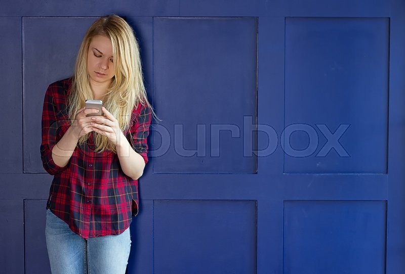Stock image of 'Cute Girl playing with her Phone on a blue Wall'