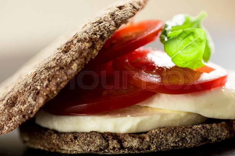Stock image of 'Sandwich with mozzarella, tomatoes and rye bread'