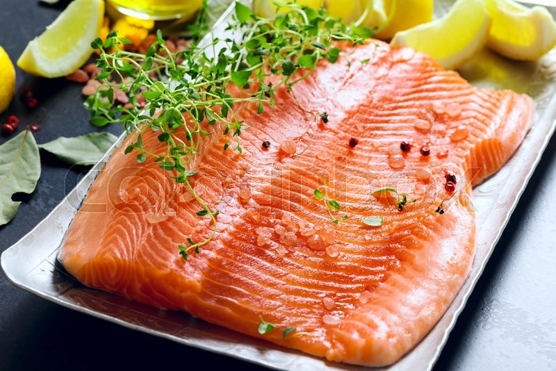 Stock image of 'raw salmon fillets on aluminium trey with lemon and spices'