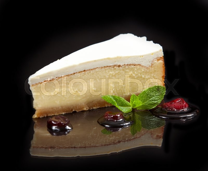 Stock image of 'cheese cake slice decorated with sweet sauce and mint leaf on black background'