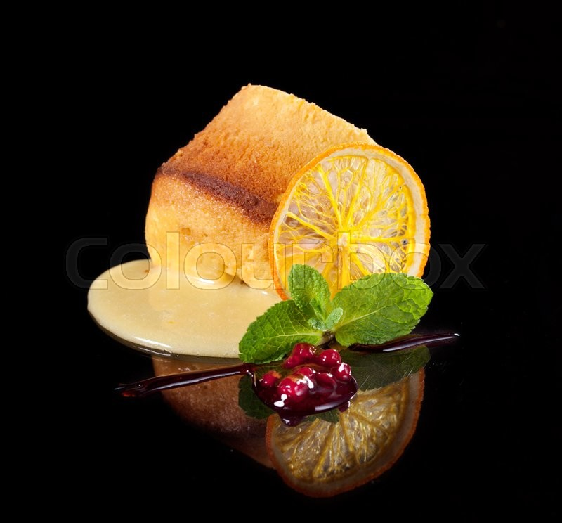 Stock image of 'fresh dessert decorated with orange and mint leaf on black background'