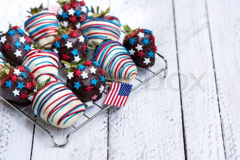 Stock image of 'Fresh strawberries in chocolate with USA flag decoration on white wooden background,selective focus'