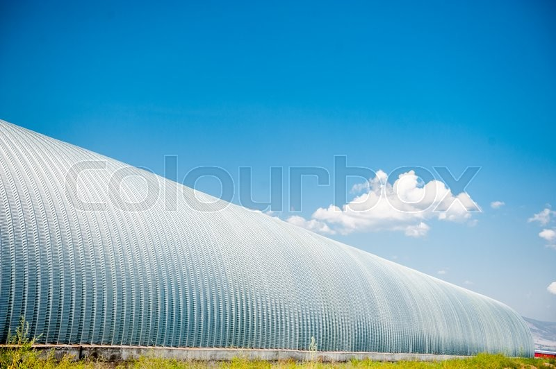 Stock image of 'Long storage for grains with the blue sky'