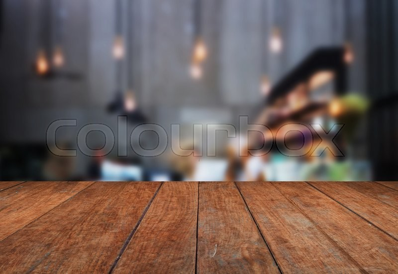 Stock image of 'Perspective table top wooden with blurred coffee shop background. product display template'