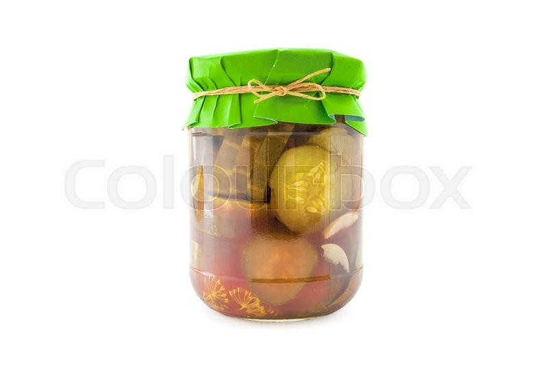 Stock image of 'Homemade pickled sliced cucumbers in glass jar with green paper wrapper. Homemade preserves, pickles. Jar of canned sliced cucumbers isolated on white'