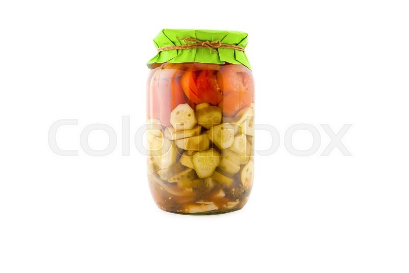 Stock image of 'Homemade pickled green and red tomatoes with cucumbers, carrots and onions in glass jar with paper wrapper. Homemade preserves, pickles. Jar of canned marinated tomatoes and cucumbers isolated'