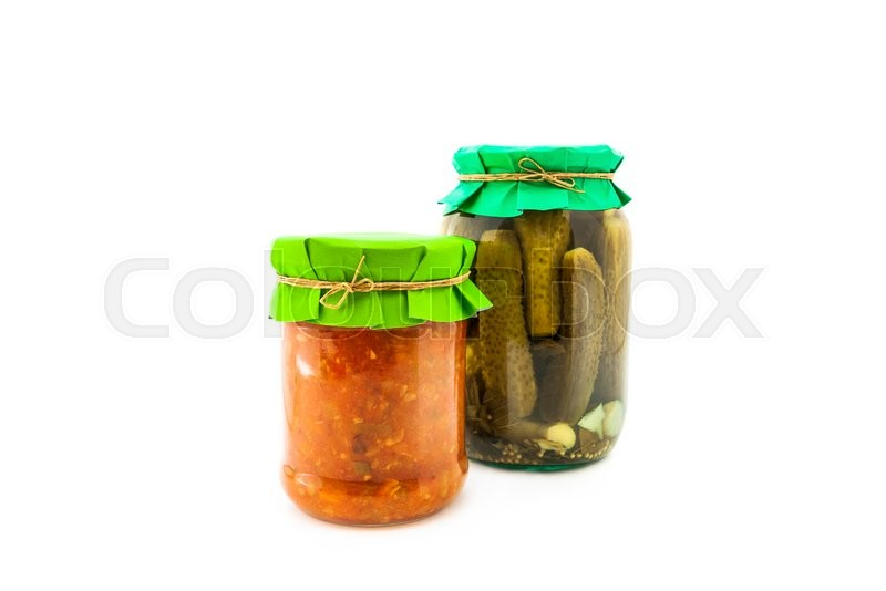 Stock image of 'Homemade pickled squash caviar with cucumbers, garlic and onions in glass jar with paper wrapper. Homemade preserves, pickles. Jar of canned marinated cucumbers with squash caviar isolated'
