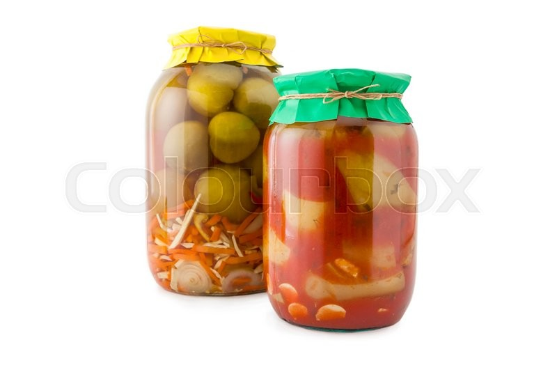 Stock image of 'Homemade pickled green tomatoes with zucchini, carrots and onions in glass jar with paper wrapper. Homemade preserves, pickles. Jar of canned green marinated tomatoes and zucchini isolated on white'