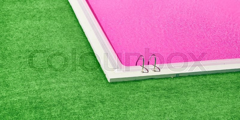 Stock image of 'Beautiful swimming pool with pink water and green grass around.Lovely pool in the garden in the park.'