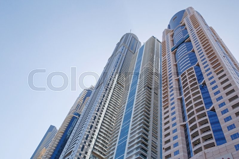 Stock image of 'Towers in Dubai over blue sky'