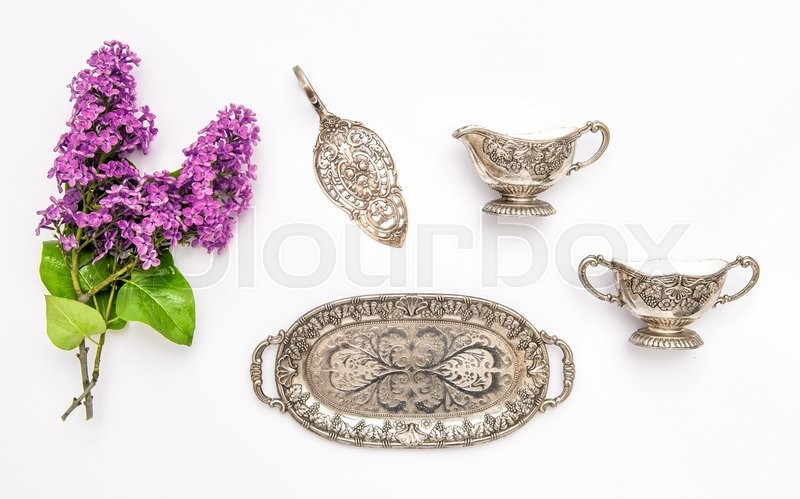 Stock image of 'Vintgae silver dishes and lilac flowers. Flat lay. Food and drink minimal background'