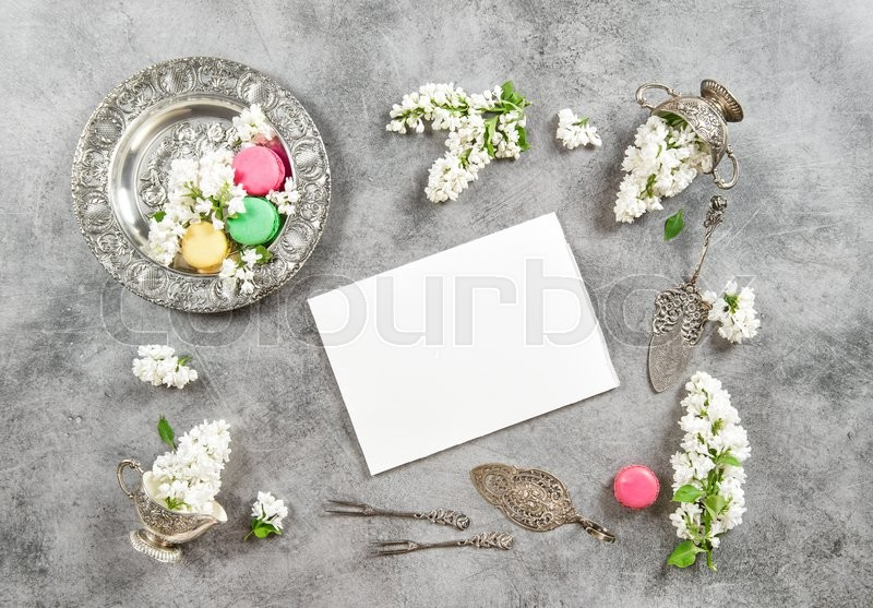 Stock image of 'Macarons cokies and white paper. Vintage style flat lay with white lilac flowers'