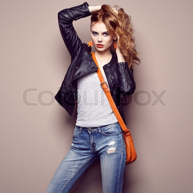 Stock image of 'Fashion portrait of beautiful young woman with red hair. Girl in blouse and jeans. Jewelry and hairstyle. Girl with handbag'