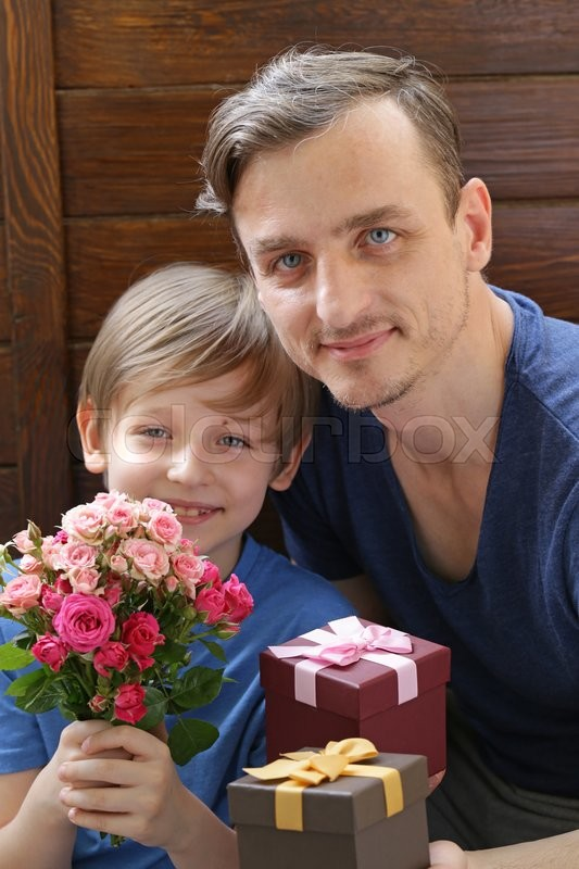 Stock image of 'Husband and son presented to  mom flowers and gifts'