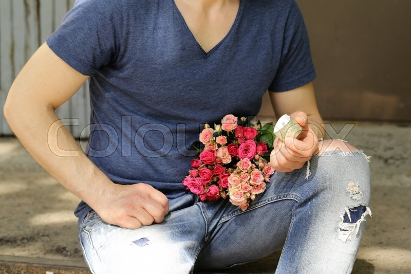 Stock image of 'Man with  bouquet of roses and diamond ring, ready to make a proposal'